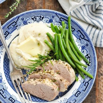 Long overhead shot of slow cooker pork tenderloin medallions with mashed potatoes and green beans