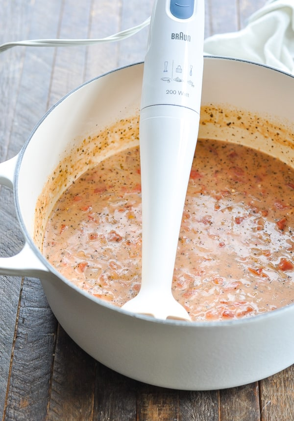 A handheld immersion stick blender in a pot of tomato bisque soup to puree