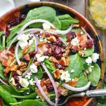 Close overhead shot of a bowl of spinach salad with pecans cranberries and feta cheese