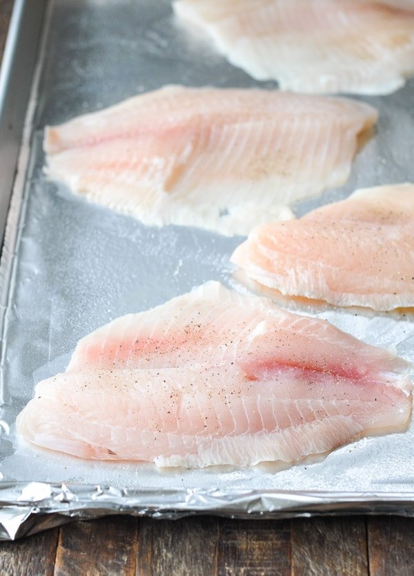 Raw tilapia on a rimmed baking sheet