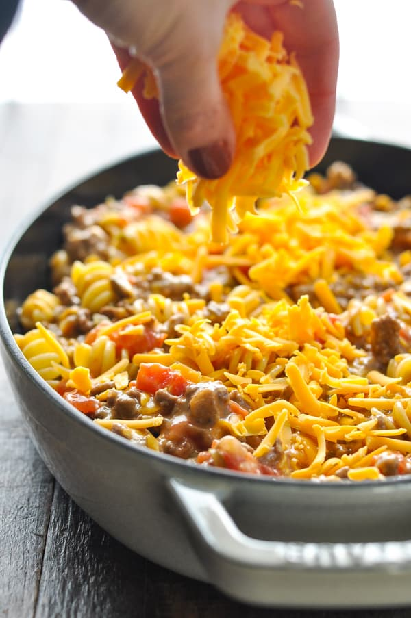 Sprinkling cheese on top of cheeseburger casserole