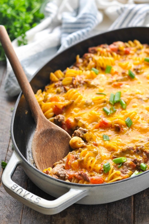 Close up front shot of cast iron dish with cheeseburger casserole and a wooden spoon