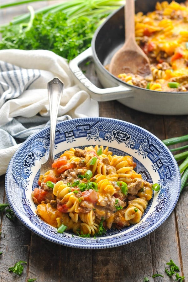 Front shot of a bowl of cheeseburger casserole with pasta on a wooden surface