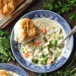 Close overhead shot of a bowl of chicken pot pie soup with biscuits on a wooden table