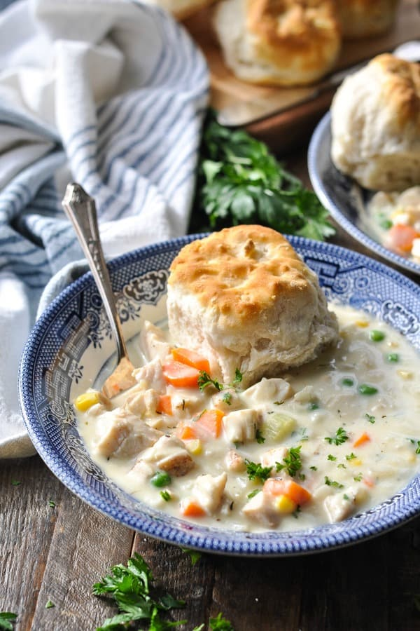 Front shot of a bowl of chicken pot pie soup with a biscuit on top and fresh parsley in the background