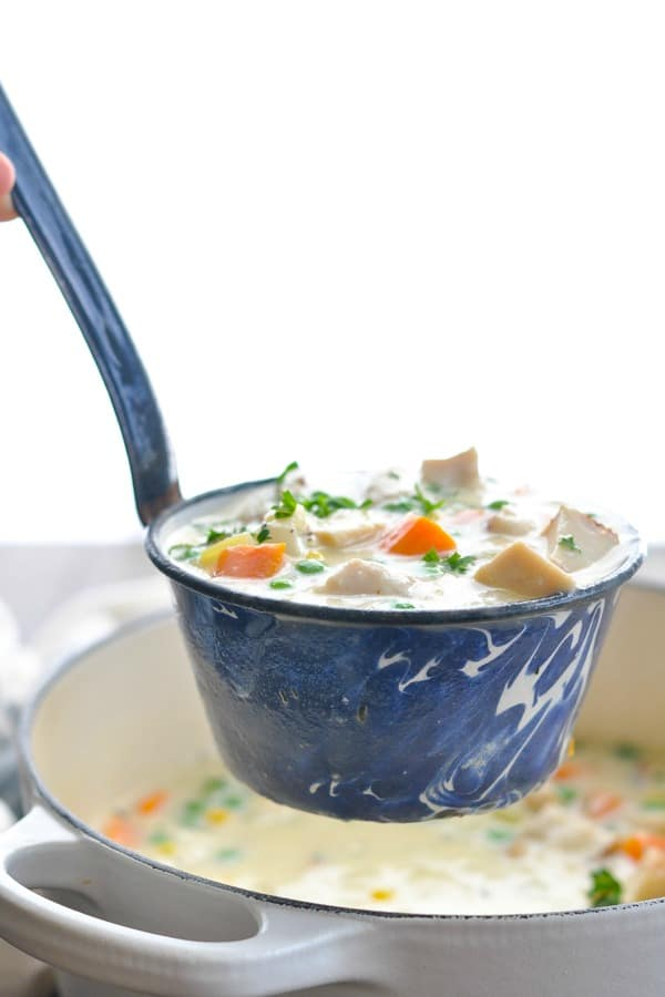 Close up shot of a ladle scooping up chicken pot pie soup