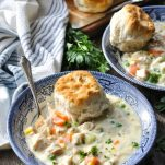 Front shot of chicken pot pie soup in a blue and white bowl on a wooden surface