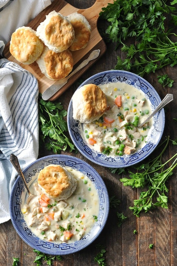Overhead shot of two bowls of chicken pot pie soup with biscuits on a wooden table