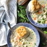 Overhead image of bowls of chicken pot pie soup from scratch topped with biscuits and fresh parsley