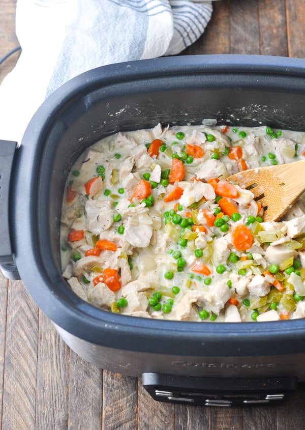 Crock Pot Chicken Pot Pie filling in a slow cooker with a wooden spoon