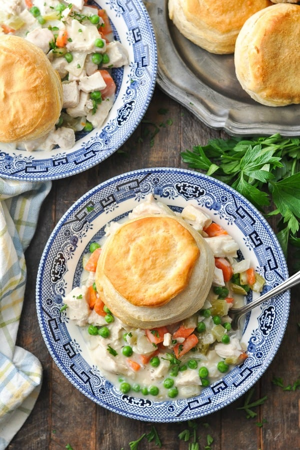 Overhead shot of a bowl of Crock Pot Chicken Pot Pie on a wooden table surrounded by fresh parsley
