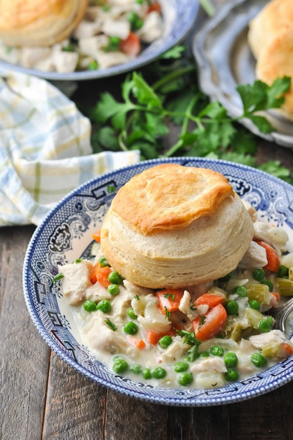 Slow Cooker Chicken Pot Pie in a blue and white bowl topped with biscuits