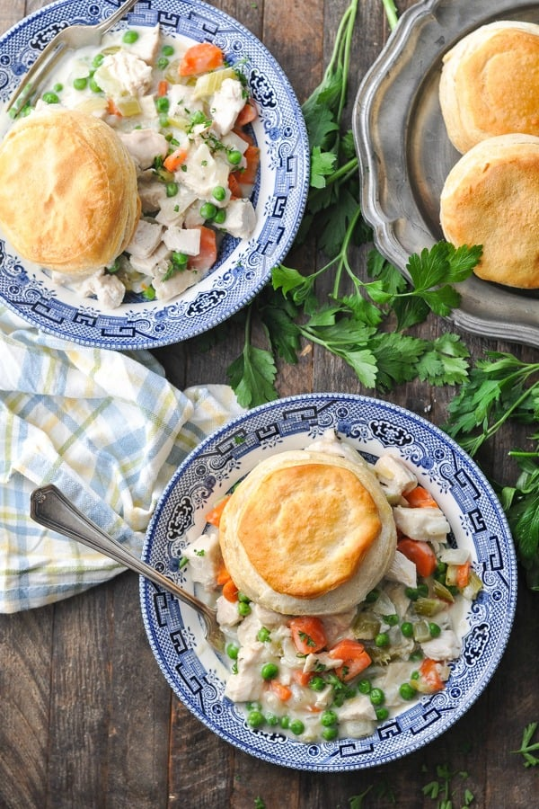 Long overhead shot of two bowls of chicken pot pie with biscuits