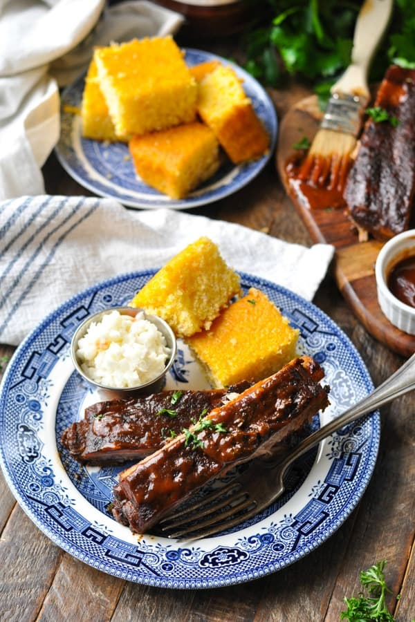 Slow Cooker Ribs on a plate with cornbread and coleslaw with more cornbread in the background