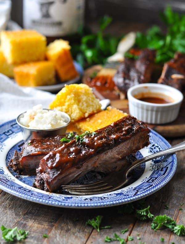 Close up front shot of slow cooker barbecue ribs on a plate with coleslaw and cornbread