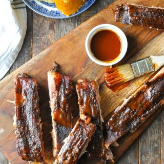 Close overhead shot of Crock Pot Ribs on a cutting board with basting brush and barbecue sauce