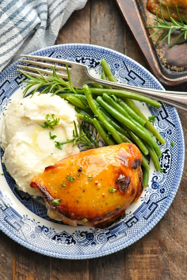 Overhead shot of honey mustard chicken thigh on a plate with mashed potatoes and green beans