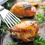 Close up shot of a honey mustard chicken thigh on a baking sheet with a spatula and fresh herbs