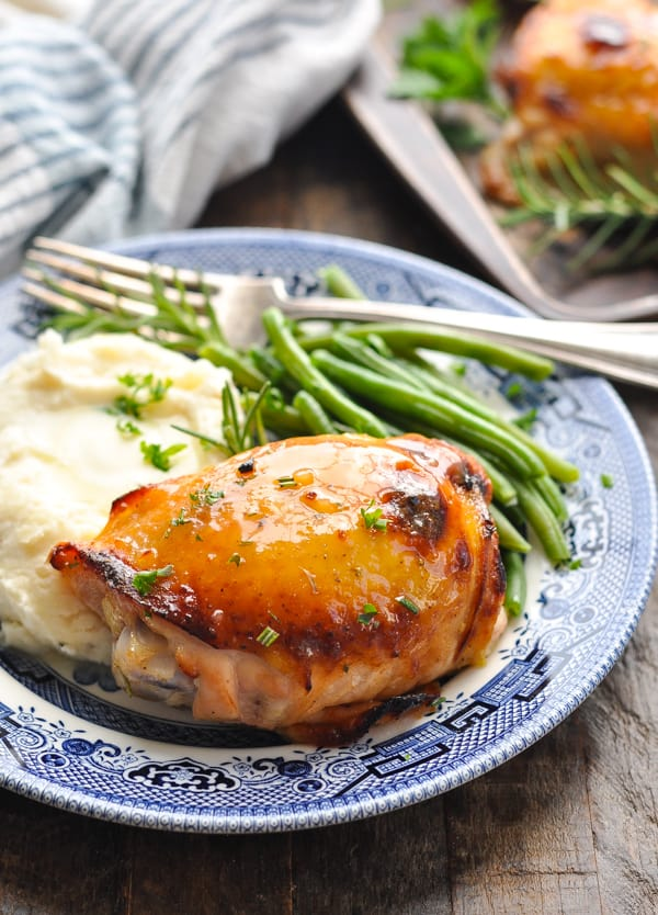 Front shot of honey mustard chicken on a blue and white plate with mashed potatoes and green beans