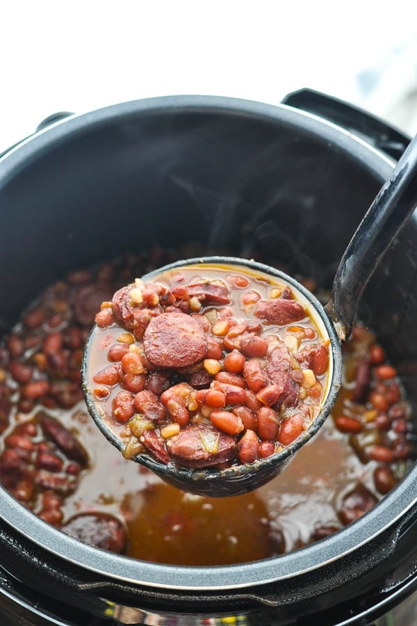 Overhead shot of ladle scooping up red beans and rice from an instant pot