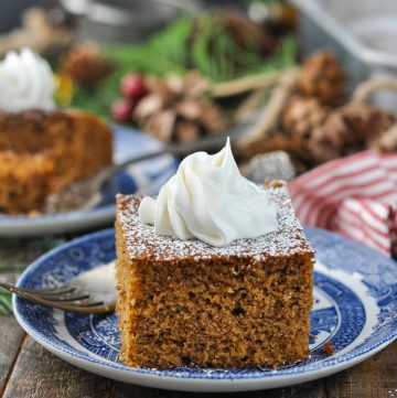 Front shot of old fashioned gingerbread cake on a plate and topped with whipped cream