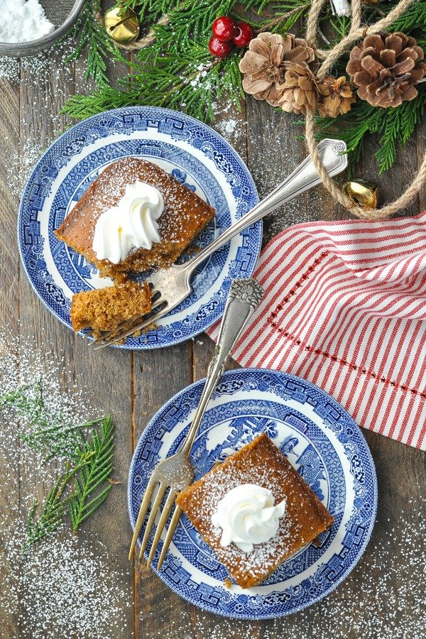Overhead shot of two plates of gingerbread cake on a wooden table