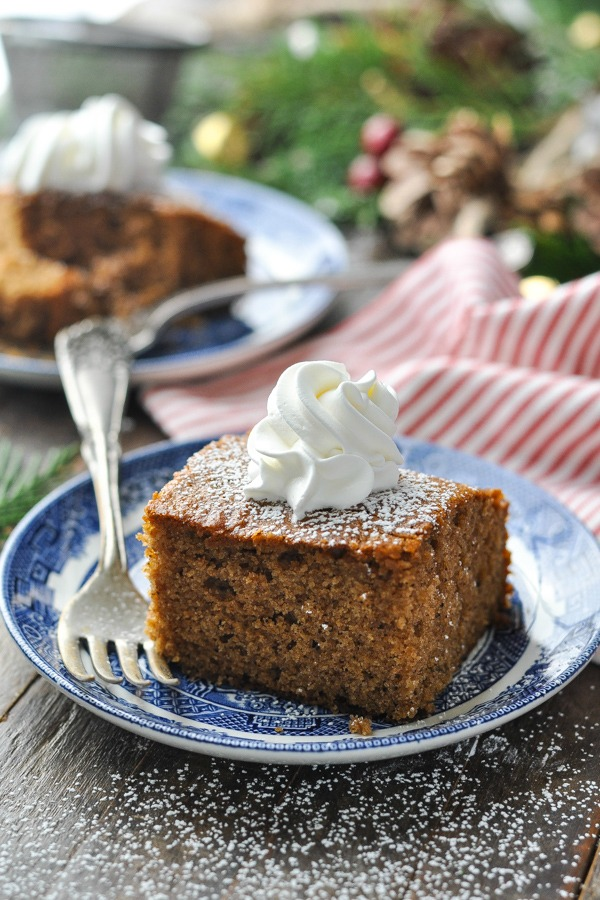 Front shot of old fashioned gingerbread cake on a plate with whipped topping