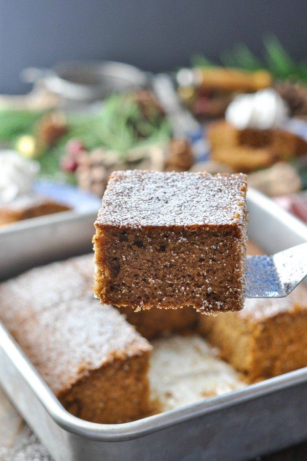 Slice of gingerbread on a spatula dusted with powdered sugar
