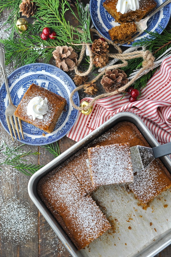Overhead shot of old fashioned gingerbread in a baking dish with slices on plates surrounding