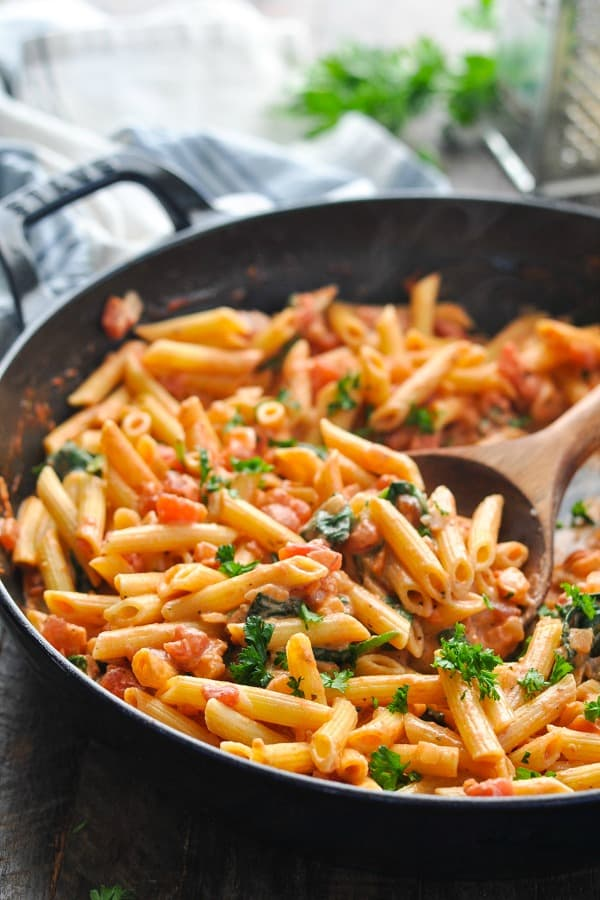 Front shot of spinach pasta tossed with tomatoes in a skillet