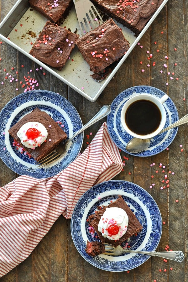 Overhead shot of plates of chocolate cherry cake with cup of coffee on the side