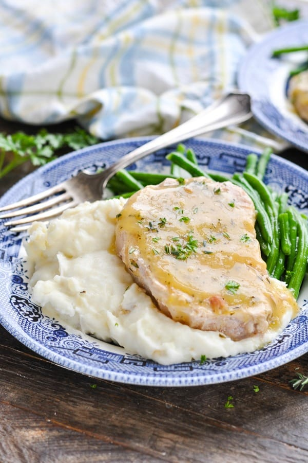 Close up shot of ranch pork chops with mashed potatoes and green beans on a plate