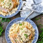 Overhead shot of boneless pork chop and rice in a bowl with creamy mushroom sauce and fresh parsley