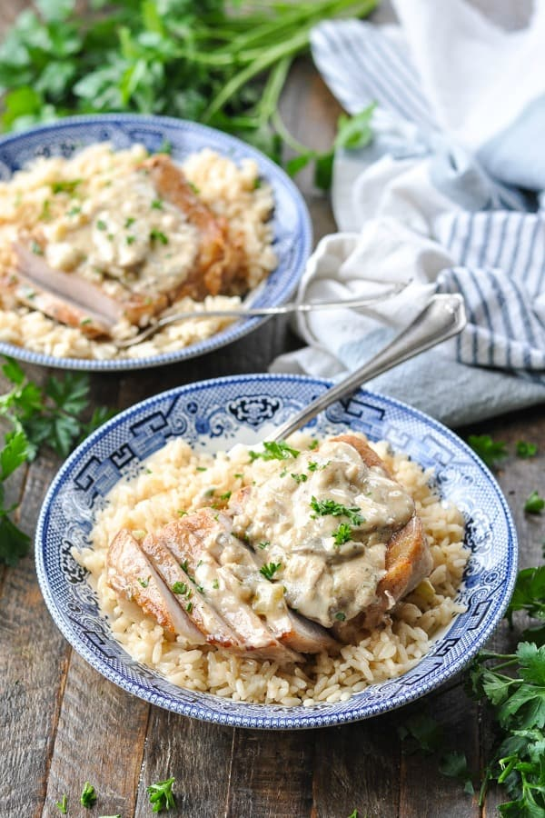 Front shot of a bowl of pork chops and rice smothered in creamy mushroom sauce