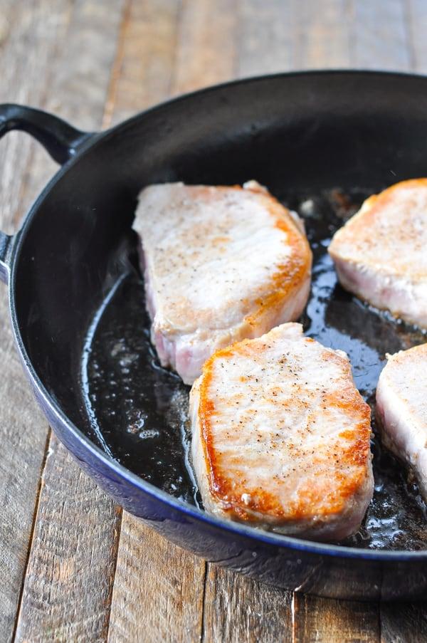 Process shot of browning boneless pork chops in a cast iron skillet