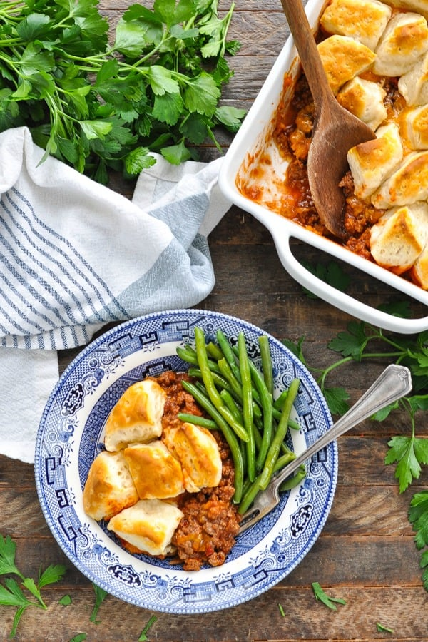 Sloppy Joe Casserole topped with biscuits and served with a side of green beans in a blue and white dish