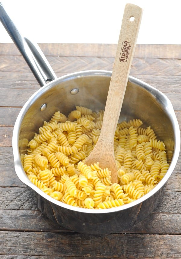 Cooked rotini pasta in a pot with a wooden spoon