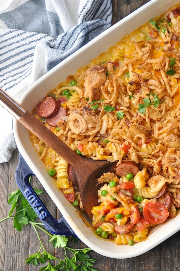 Overhead shot of smoked sausage pasta baked in a blue casserole