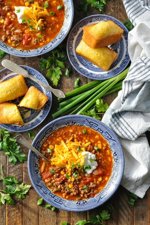 Overhead shot of bowls of chili with plates of cornbread