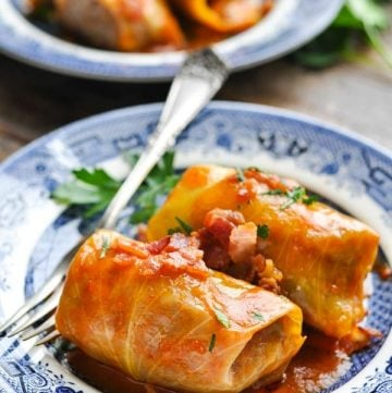 Close up front shot of stuffed cabbage rolls on a plate garnished with bacon and parsley