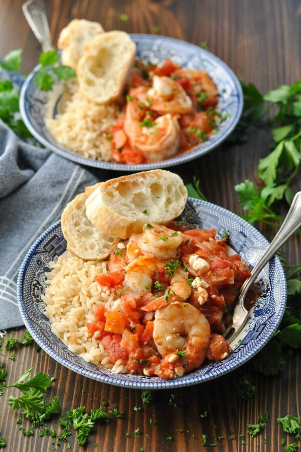 Front shot of two bowls of baked shrimp in the oven garnished with herbs and crusty bread
