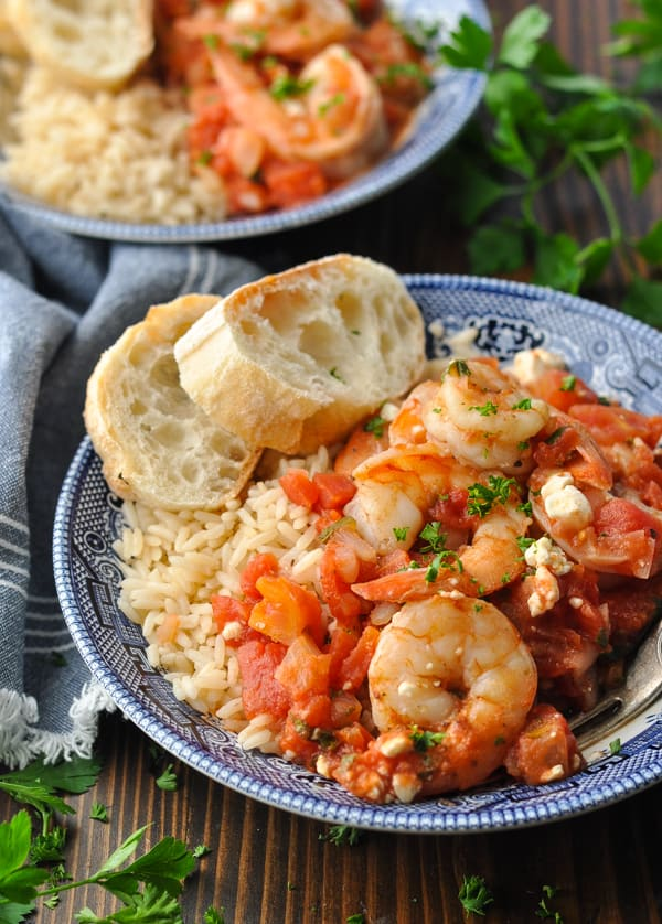 Front shot of two bowls of baked shrimp with tomatoes and feta