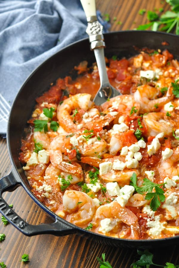 Close up front shot of baked shrimp with tomatoes and feta in a cast iron skillet