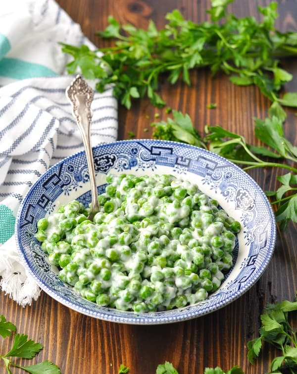 Front shot of a bowl of creamed peas on a wooden surface