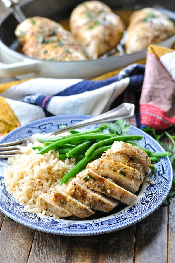 Front shot of baked chicken breast on a plate with rice and green beans