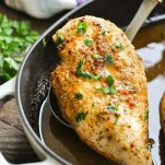 Close up shot of oven baked chicken breast garnished with fresh parsley
