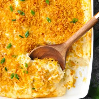 Close overhead shot of cheesy potato casserole in a white dish with wooden serving spoon