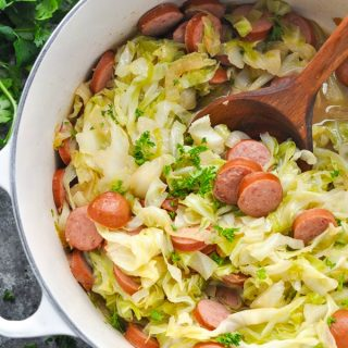 Close overhead shot of sausage and cabbage in a dutch oven