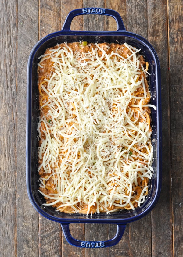 Spaghetti casserole in a blue dish before baking