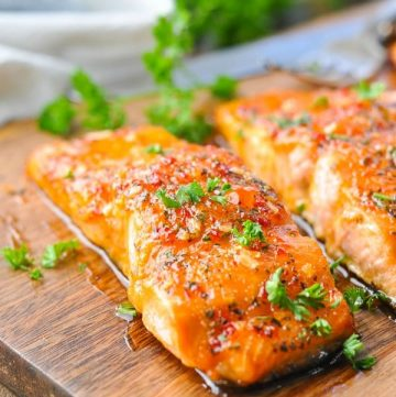 Close up front shot of glazed salmon on a cutting board